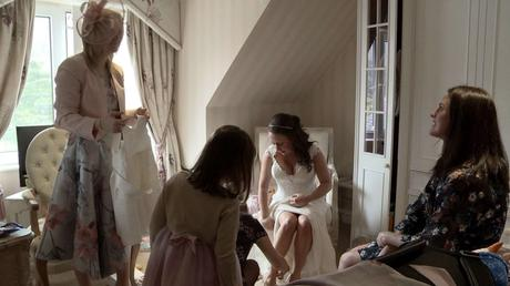 the bride sits in a cream armchair in the wordsworth hotel whilst her friend kneels down and helps her put on her wedding shoes