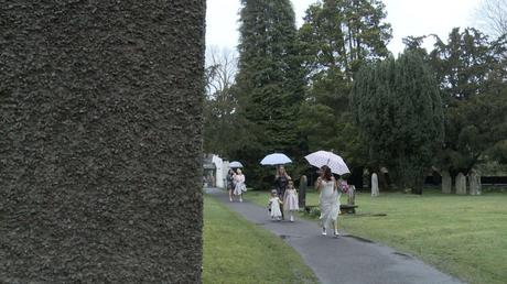 a bride and her flower girl hold umbrellas as they walk in the rain through the gardens at St Oswalds in Grasmere before her wedding ceremony