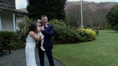 the bride and groom try and get their daughter the flower girl to smile for the wedding photographer as they pose in the gardens of the wordsworth hotel with the scenic lake district hills in the background
