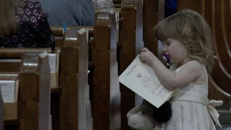 a little flower girl with a dummy in her mouth curiously opens up the order of service for her mommy and daddys wedding at St Oswalds church in Grasmere