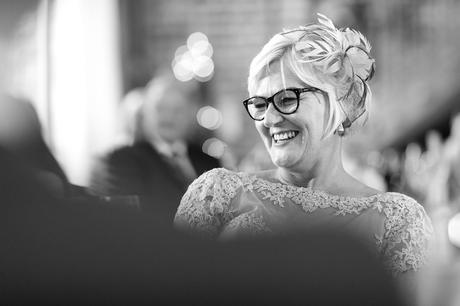 Bride's mom laughing and smiling during speechs