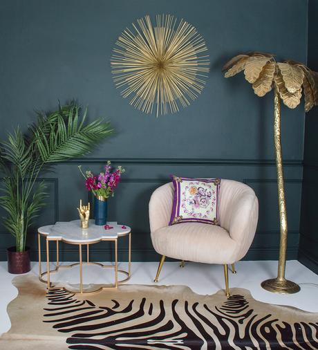 Dark and moody living room inspiration. Pair dark walls with a zebra cowhide rug, gold palm tree floor lamp and a blush pink velvet armchair, for an uber glam, eclectic living room.