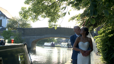 the bride and groom stand on the tow path by the canal under a shady tree with the canal bridge in the background