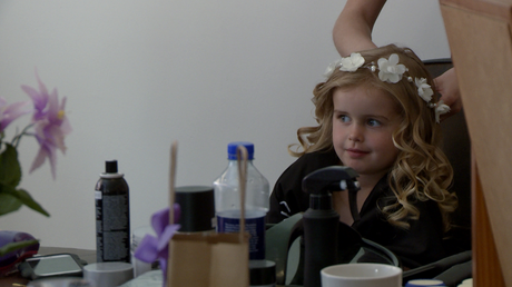 a young flower girl has a white flower crown added to her curled hair by the hair dresser for her Mum's wedding in Burscough