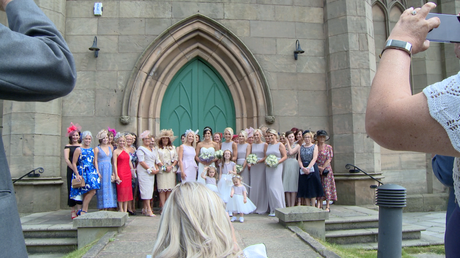 laura wade the wedding photographer ducks down to get a large group shot outside st johns churchs green doors