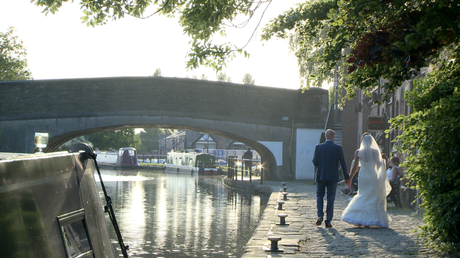 the bride and groom walk back towards the Blue mallard down the tow path of the canal as the sun begins to set behind the trees