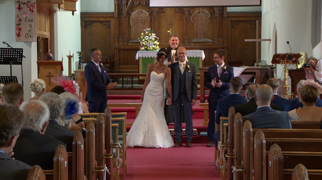 the bride and groom face their wedding guests and wedding videographer as they cheer and clap them being announced as the new Mr and Mrs Disley at St Johns in Burscough lancashire