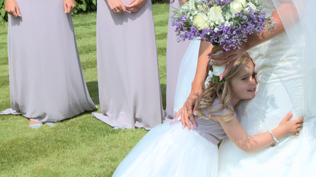 a flower girl gives her Mum in her wedding dress a big cuddle as the bridesmaids smile standing in her parents garden in Holmeswood