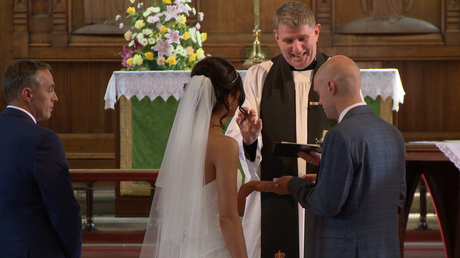 the priest at St Johns church makes a ting sign with his fingers to show the groom how to push the wedding ring on