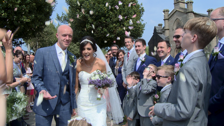 the bride laughs and ducks down as guests shower them in natural flower confetti outside their church in burscough