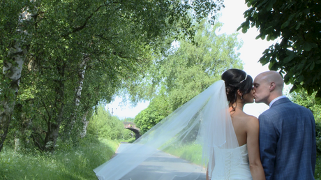 a bride and groom kiss on a country lane in Burscough and Lathom