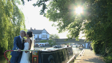 the bride and groom have a kiss standing on a canal boat outside Burscough wharf as the sun peeks through the trees for their wedding video