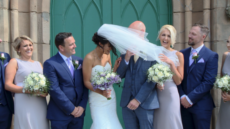 the brides veil gets blown in front of the grooms face during their wedding photos outside st johns church in burscough