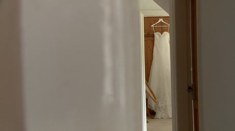 a lace wedding dress hangs on a wardrobe in a far room