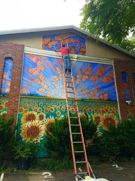 Cedar Lee assisting in installation of Hector Hernandez Monarca Mural in Portland, OR