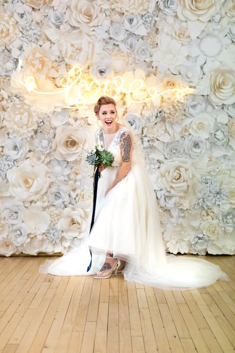 River Mills Ballroom Wedding Photography tattooed bride stands in front of paper flower wall