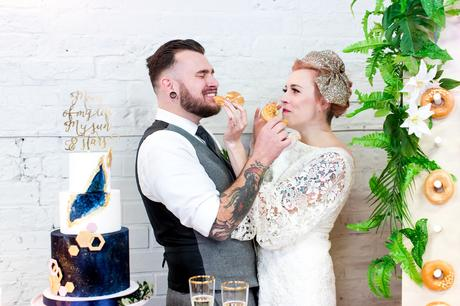 Alternative Tattooed wedding couple eat a donut together