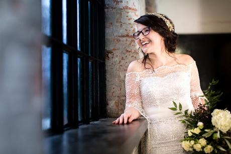 Beautiful bride looks out of mill window at River Mills Ballroom