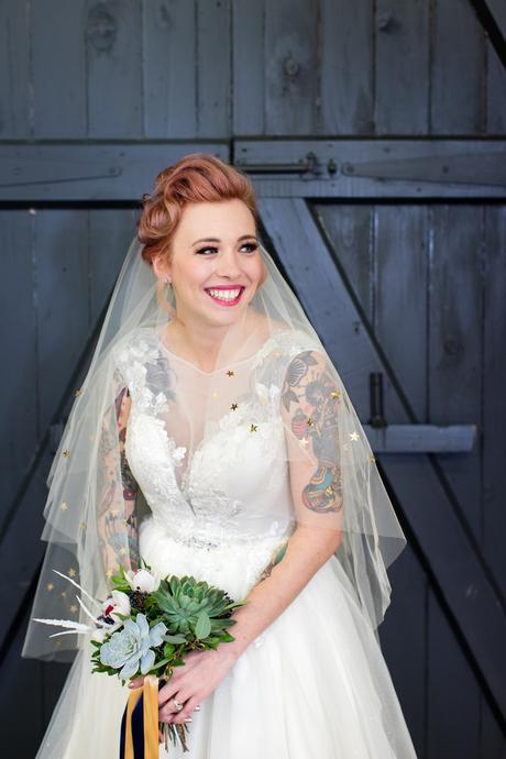 River Mills Ballroom Wedding Photography Tattooed bride wearing dress from Legend Bridal in front of gray blue door