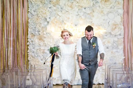 River Mills Ballroom Wedding Photography alternative and quirky wedding couple walk up aisle in front of flower wall