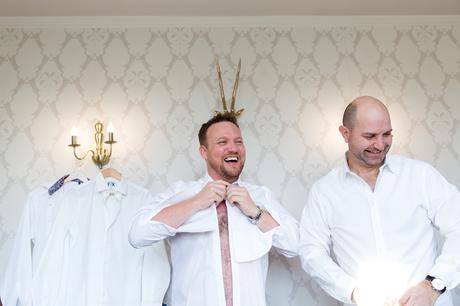 York Wedding Photography at Hornington Manor Farm groom with Stag horns behind his head as he gets dressed