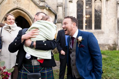 Candid moment of groom smiling at baby at York Wedding
