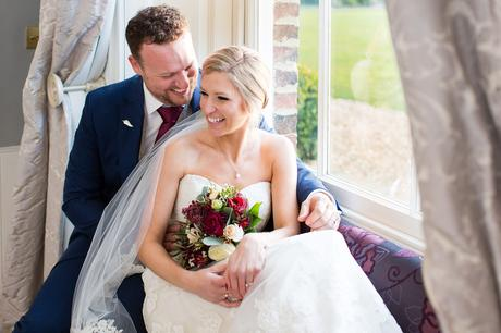 Bride and Groom sitting in the window seat at Hornington Manor Farm