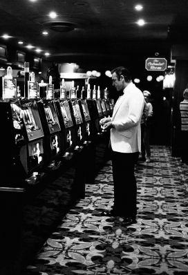Sean Connery takes a solitary break to play the slots. Note the dinner jacket's angled hip pockets and the long back vents. Photo by Terry O'Neill, 1971.