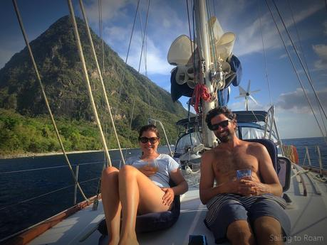 two people on a sailboat with a tropical island