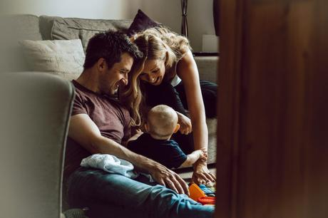 a dad sits on the floor of their living room in Sale Manchester next to his 7 month old little boy as Mum leans in with a huge smile to make him smile as the photographer sits by the door capturing a relaxed family moment at home