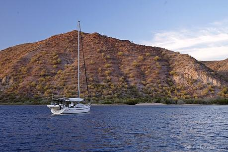 Sailboat at anchor in front of rugged desert hills off Baja