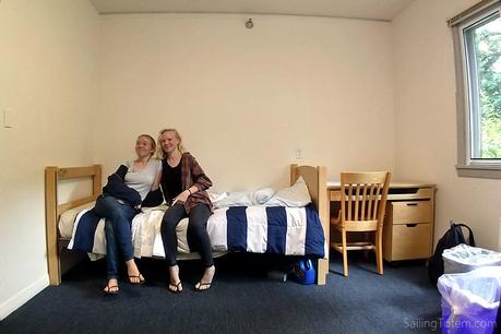 Two girls sitting on the edge of a bed in a college dorm room