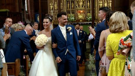 the bride and groom walk back up the aisle at St Savious church in wirral and the bride holds a classic ivory rose bouquet