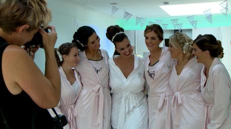 the bride cuddles up with her bridesmaids in their matching wedding robes as they pose for their wedding photographer Jane Hockey