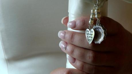 you are always in my heart locket hanging by the brides fingers as she holds her wedding bouquet tied in ivory ribbon tightly before getting married