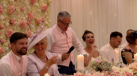 the father of the bride has everyone laughing during his wedding speech in front of a stunning pink and ivory flower wall at thornton hall