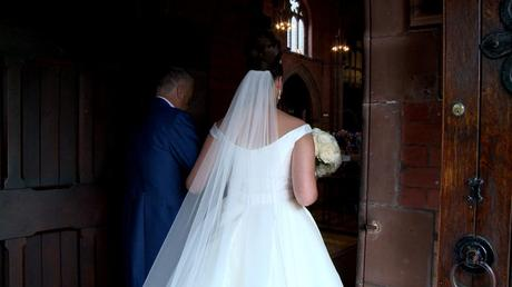 the bride links her dad's arm in the doorway of St Saviours church before walking down the aisle captured on her wedding video