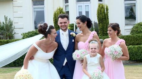 the bride and bridesmaid laugh at each other as the groom stands smiling inbetween as they pose for photos at Thornton manor