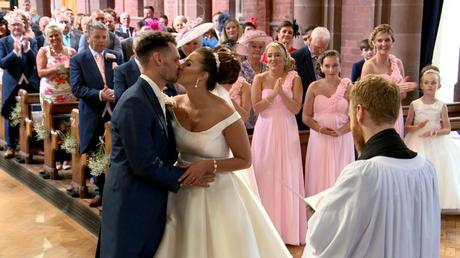 you may kiss the bride as the wedding guests smile and clap behind them at St Saviours church near Birkenhead
