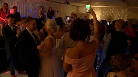 a full dancefloor of wedding guests at Thornton hall hotel in the wirral dancing and singing along with northrn lights band on stage