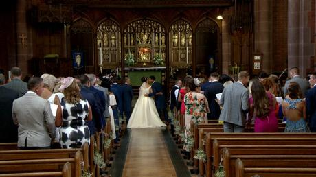 the groom greets his bride with a kiss after she's walked down the traditional church aisle at St Saviours in Birkenhead