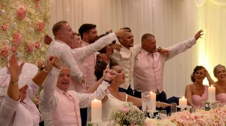 the bridal party are standing and swaying to Sweet Caroline after the wedding speeches at thornton hall