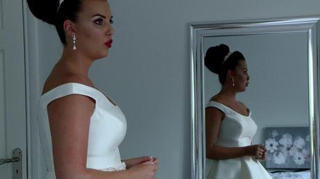a classic old hollywood style bride takes a deep breath pouting her red lips with her reflection in the mirror behind her on the wedding video
