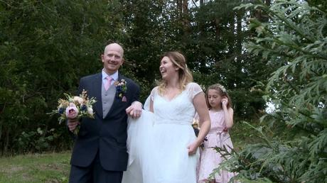 a groom smiles at the videographer as the bride laughs and holds his hand walking down the hill at Abel's Harp