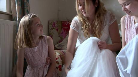 two flower girl daughters laugh with their mum as they try to help her get her white glitter irregular choice wedding shoes on for the videographer
