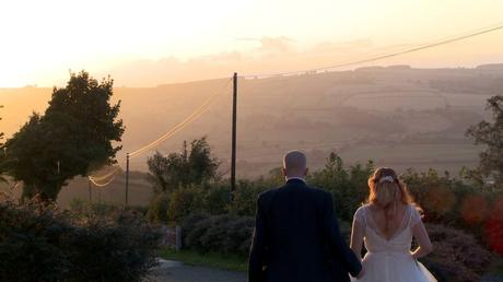 a stunning light peeks over the welsh hills as a bride and groom walk away from the videographer holding hands