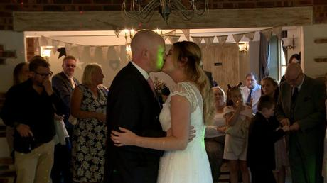 the bride and groom enjoy a kiss during their first dance captured by thr wedding videographer at Abel's Harp in Bromlow