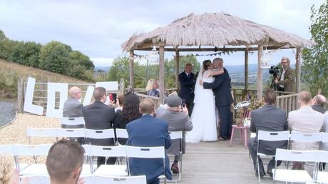 the bride and groom kiss as guests sat in the white sites during the outdoor ceremony at Abel's harp all clap and cheer for the wedding video