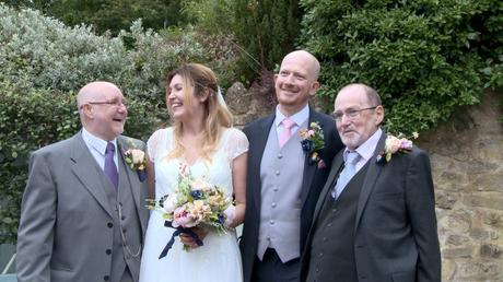 a bride smiles at her Dad during a group shot as the Groom looks at the camera with his dad