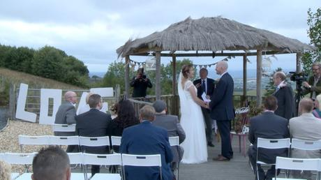 a video still of an outside ceremony at abel's harp in Shrewsbury with the bride and groom holding hands to say their wedding vows